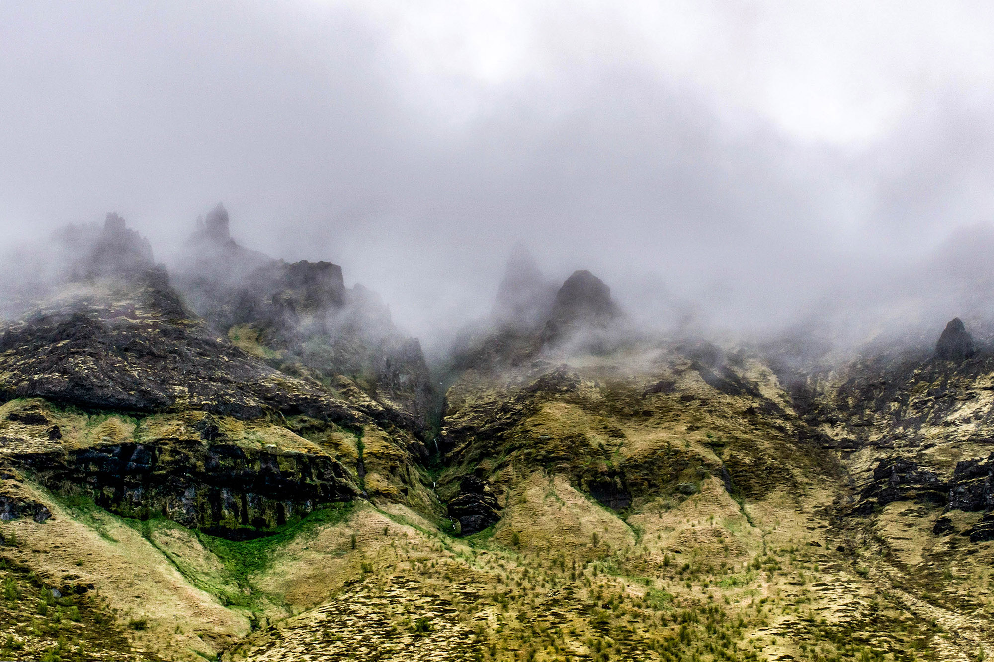 Epic surreal Landscape in Iceland with green grass and rocks in fog clouds foggy mountains