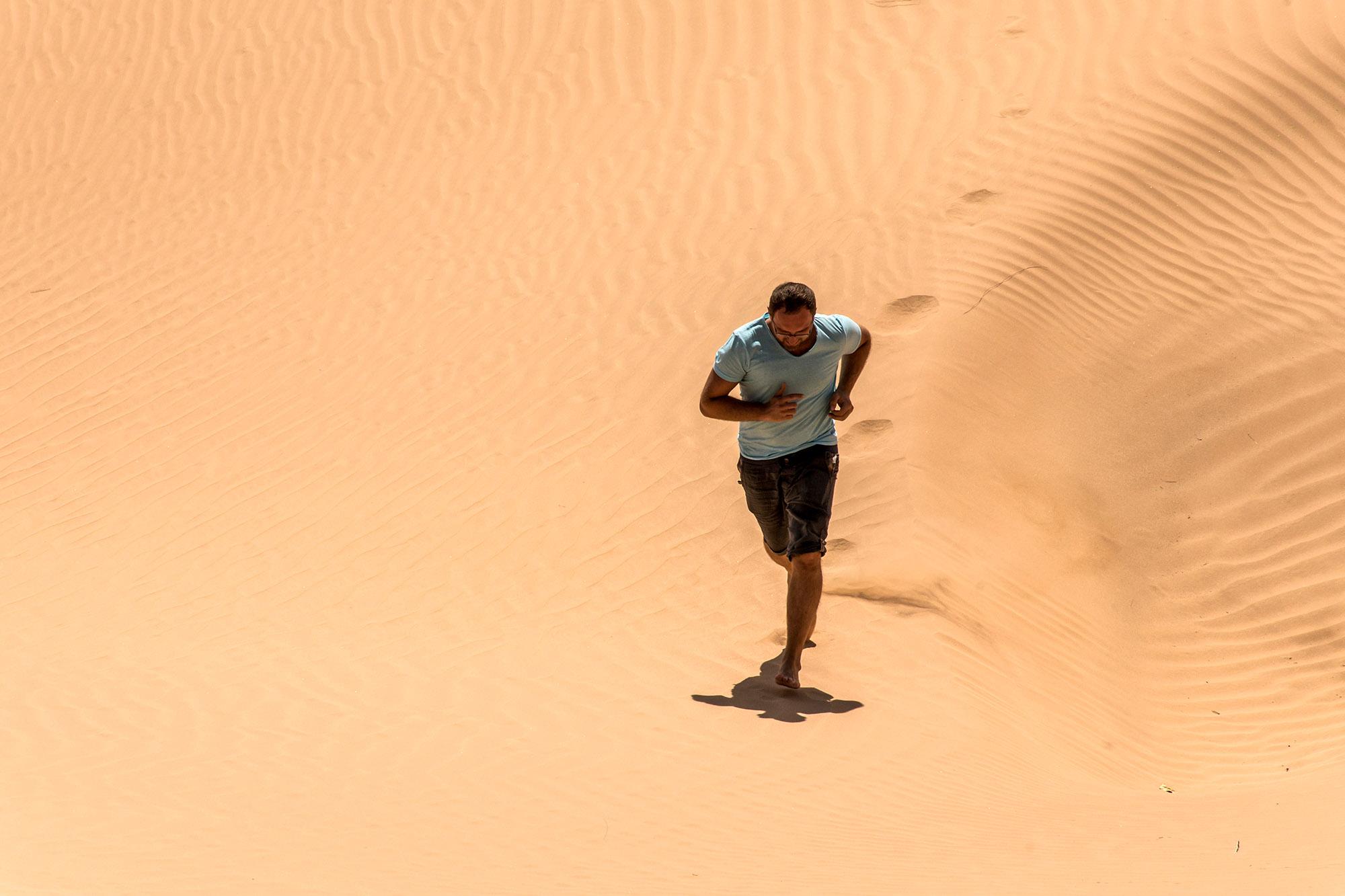 Man tourist in desert rub al khali in Oman running in sand 3